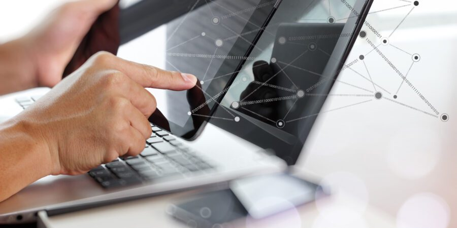 Man holding tablet with laptop on desk and illustration of virtual connections.