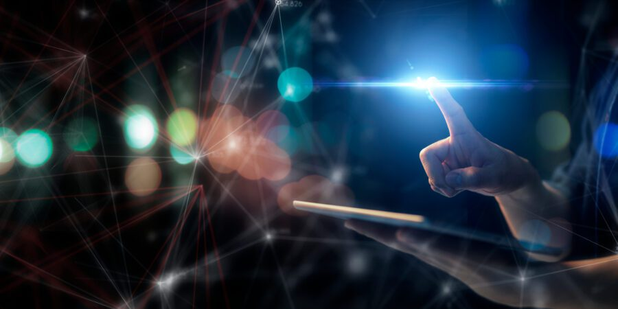 Man holding tablet and holding finger out to touch a blue light.